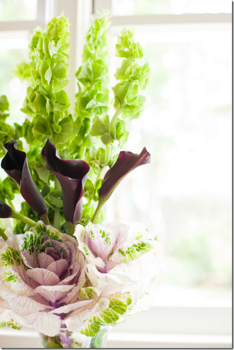 black cala lilies bells of ireland and pink cabbage arrangement