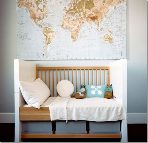 world map centered above a modern crib in a nursery designed by brad
