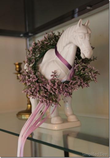 misty floral wreath around horse figurine